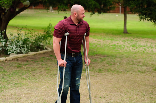 Muscular bald man on crutches