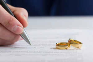 A person signing a divorce settlement with two wedding bands