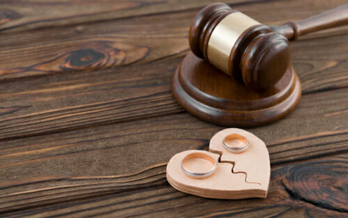 A gavel and two wedding rings on a broken, wooden heart to dignify divorce in Maryland.